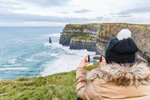 52956158 - tourist taking a photo with smartphone about cliffs of moher